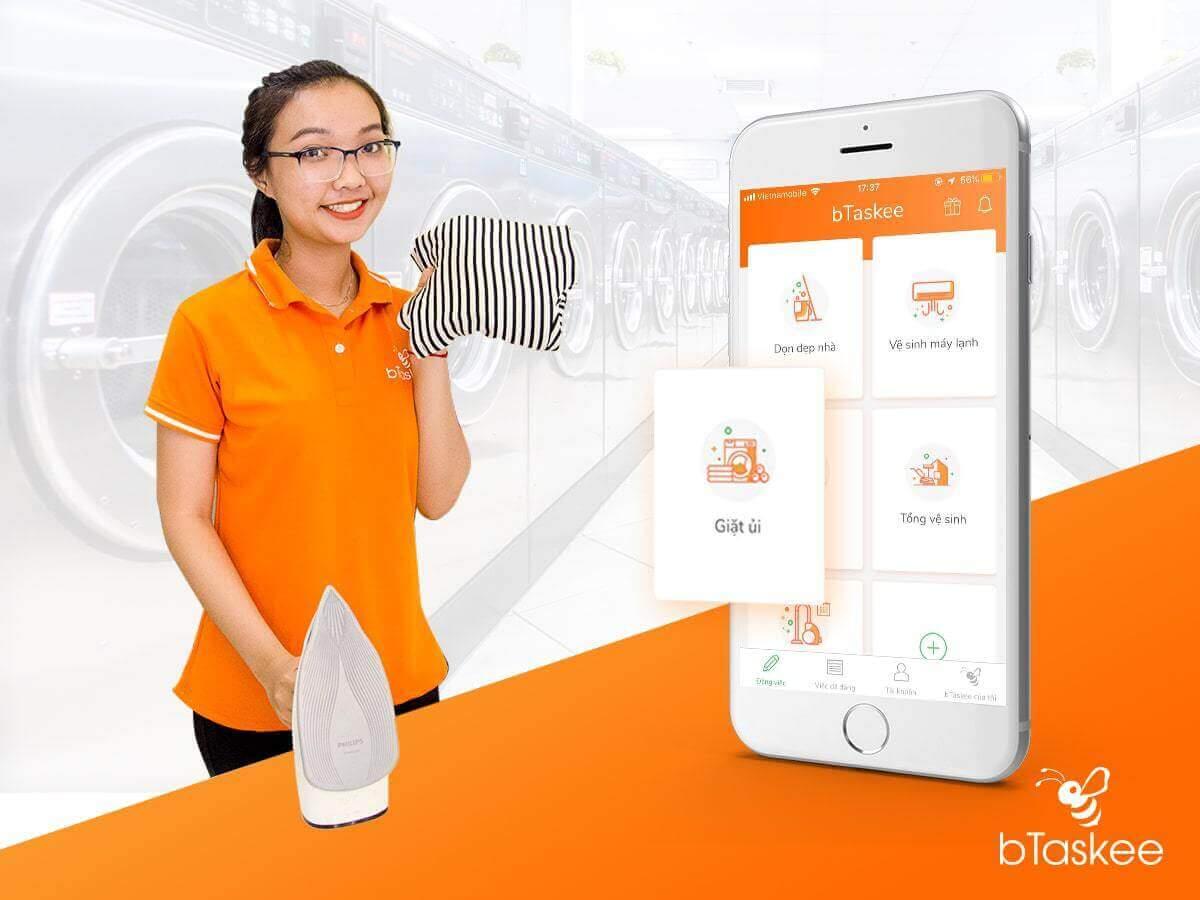 cô gái cầm khăn và bàn ủi với màn hình giao diện app btaskee bên cạnh