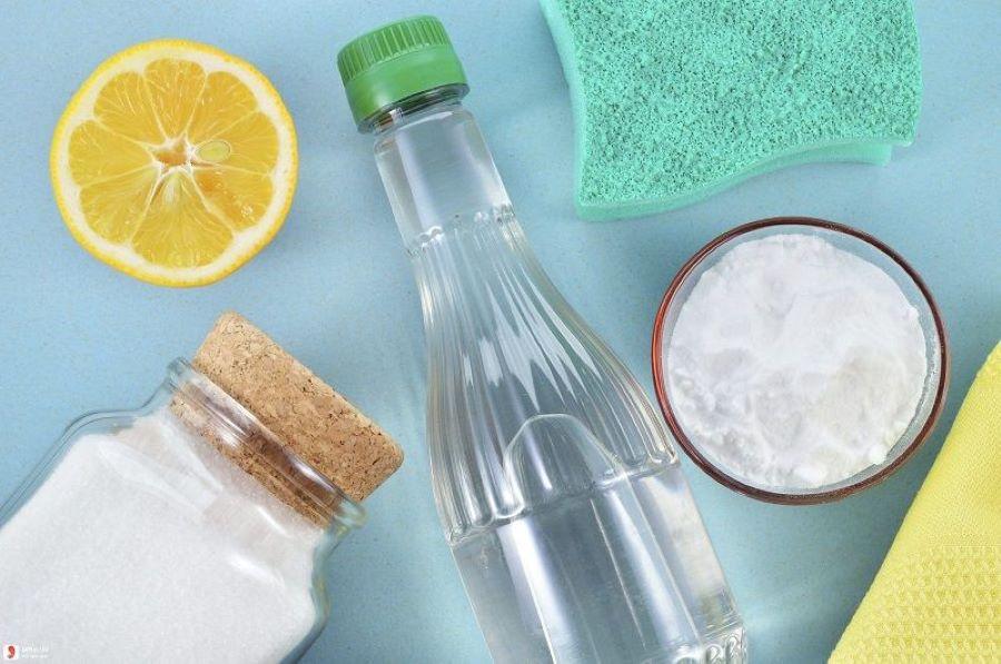hủ baking soda và chai giấm, nửa lát chanh nằm trên bàn