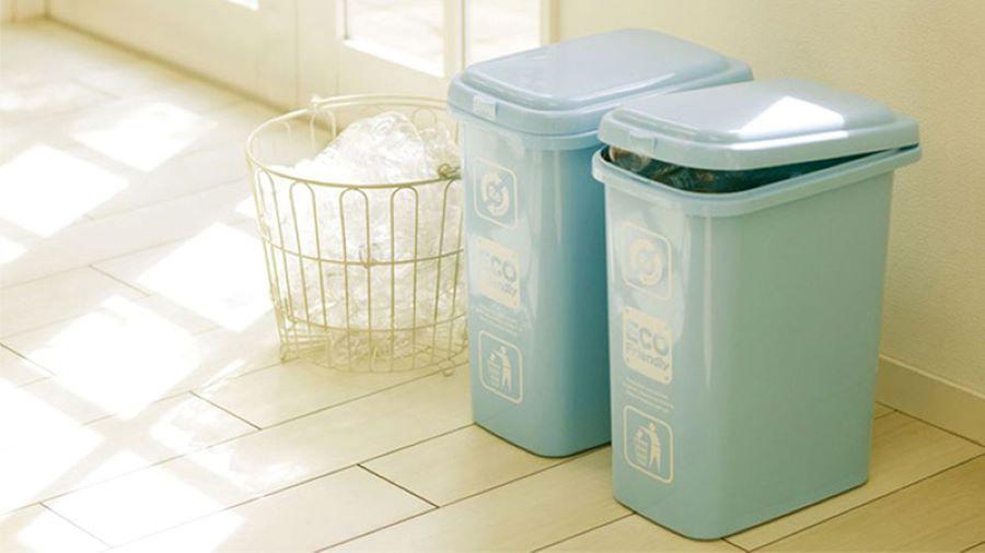 hai thùng rác màu xanh mint bên cửa sổ