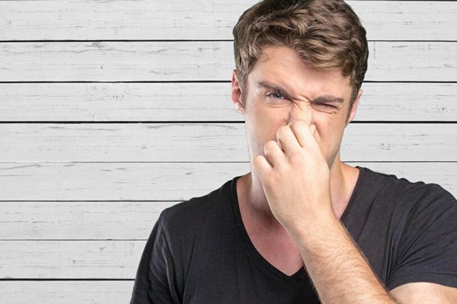 đàn ông đang bịt mũi vì mùi sơn gỗ khó chịu