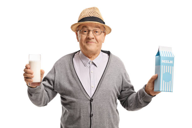 Mature man holding a glass of milk and a milk carton isolated on white background
