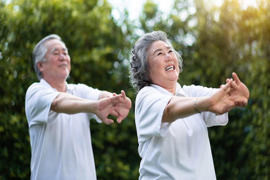 2 cụ già đang vươn tay ra trước tập thể dục