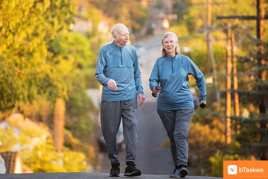 2 ông bà mặc áo khoác xanh, quần dài xám đang đi bộ.