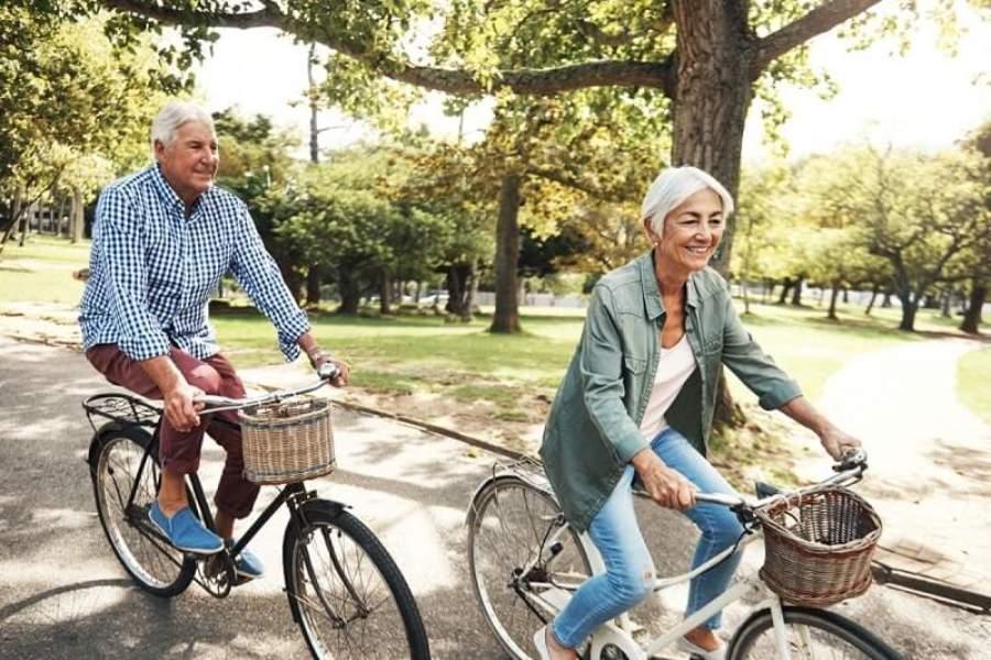 2 ông bà đang đạp xe trên đường