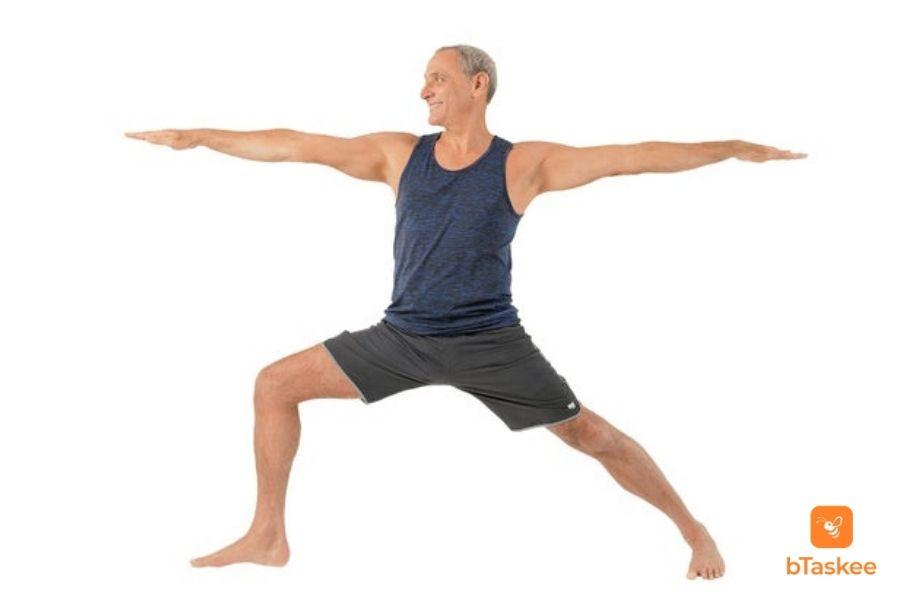 Ông bác đang thực hiện tư thế chiến binh trong bài tập yoga cho người cao tuổi. Chân phải cong, chân trái duỗi, 2 tay sang ngang, mắt hướng về bên phải
