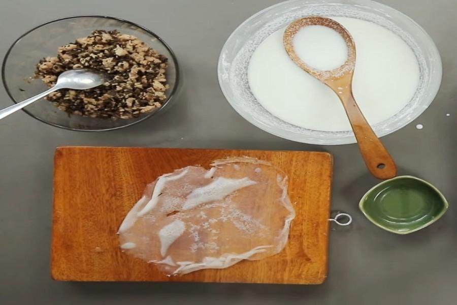 Bánh cuốn được đặt trên mặt thớt, có tô thịt góc 11h và tô đựng bột ở góc 1h