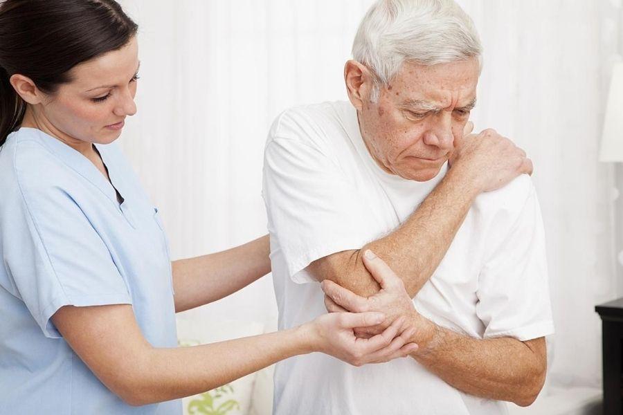Y tá đang hỗ trợ cụ già bị đau vai