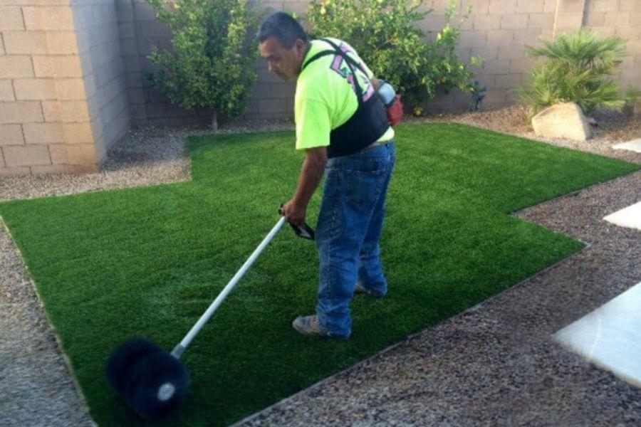 người đàn ông vệ sinh thảm cỏ nhân tạo